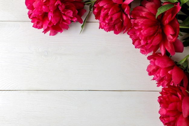 Frame of beautiful bright pink peony flowers on a white wooden background. top view. space for text
