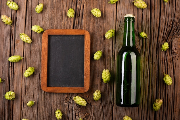Frame and beer bottle on wooden background