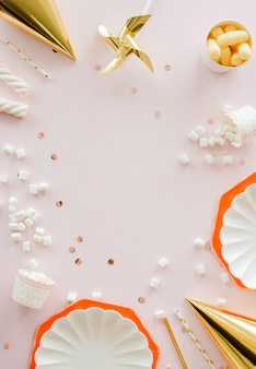 Frame of birthday party supplies. dusty pink background