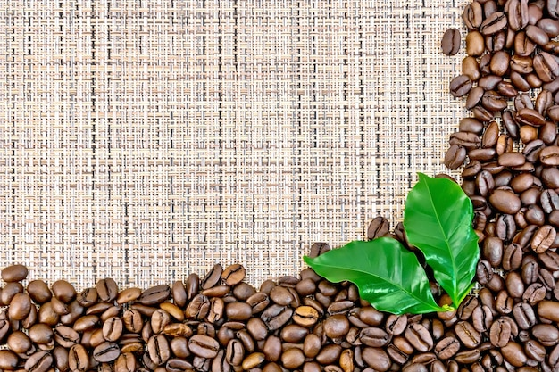 Frame of black coffee beans with leaves on brown coarse woven fabric