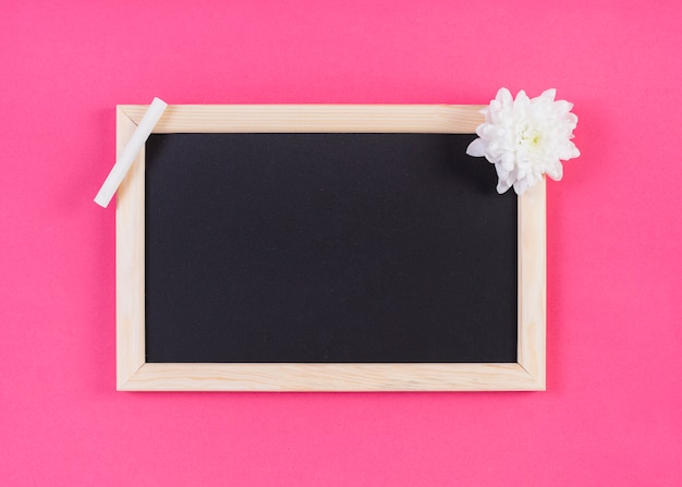 Frame blackboard with chalk and flower