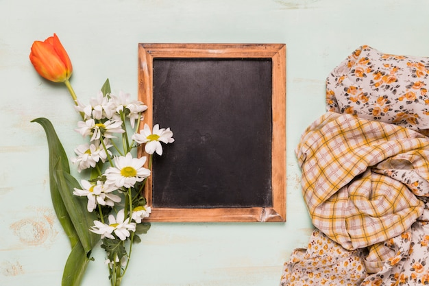Frame blackboard with flowers and shawls