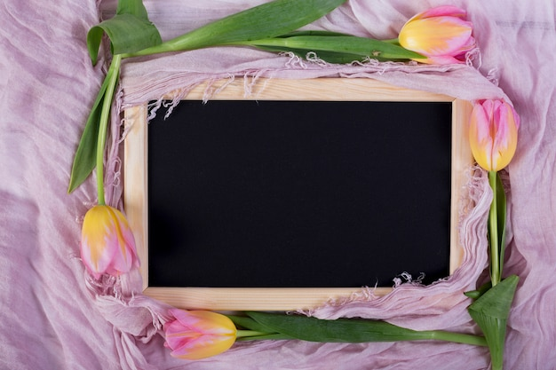 Frame blackboard with tulips on shawl