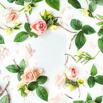 Frame of blank paper, pink roses, branches, leaves and petals isolated