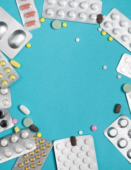 Frame blister packs of colorful pills with one  on blue.