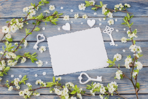 Frame of blooming cherry twigs, keys, hearts and empty sheets of paper