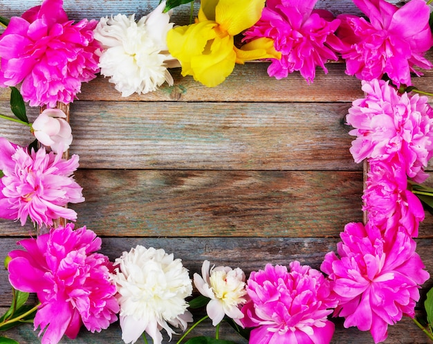 Frame bouquet of pink and white peonies flowers close-up on wooden retro background with copy space