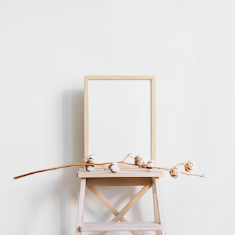 Frame behind branch on stool