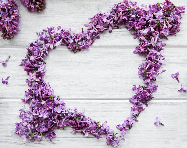 Frame of branches and flowers of lilac in the shape of a heart