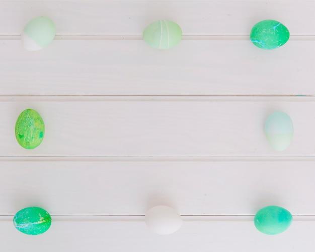 Frame of bright easter eggs on desk