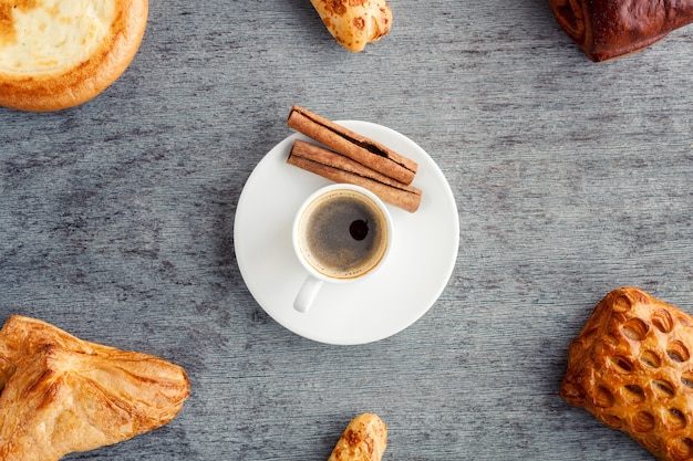 A frame of cakes and croissants around a cup of coffee