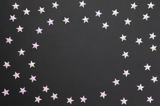 Frame of chaotic numerous pearl confetti in form of small stars on black paper background, copyspace. celebration, holidays, sales, fashion .