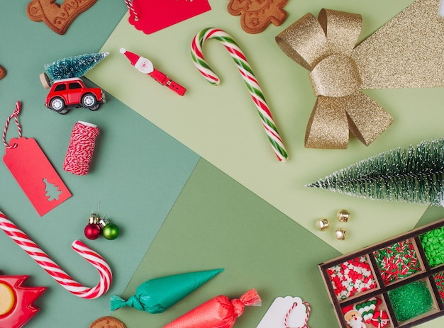 Frame of christmas gingerbread cookies, icing bags, sprinkling and decor on green color surfaces with blank space for text. top view, flat lay.