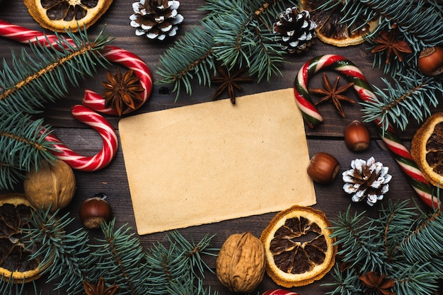 Frame of christmas tree cones oranges caramel cane nuts on dark wooden background. copy space. flat lay. old paper for text.