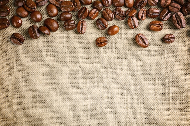 Frame of coffee beans on color sackcloth wall