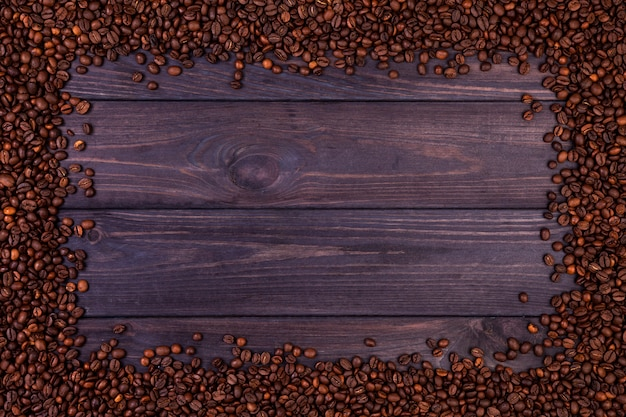 Frame of coffee beans on dark wooden background. top view with copy space