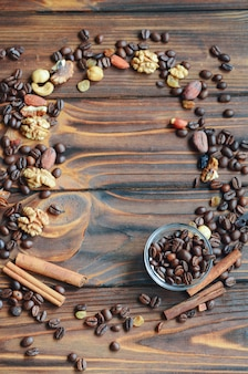 Frame of coffee beans, raisins, nuts and cinnamon on natural wooden background with copy space for your text