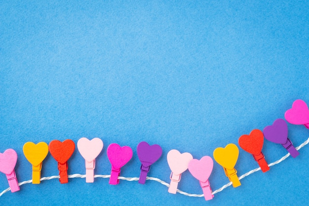A frame of colored wooden hearts hanging on a rope on a blue background.