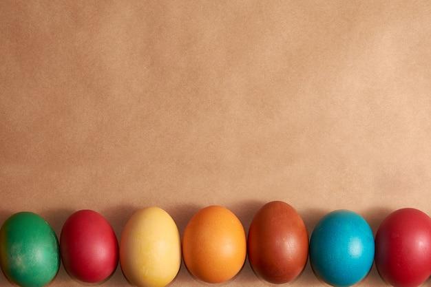 Рама красочные пасхальные яйца на коричневом фоне