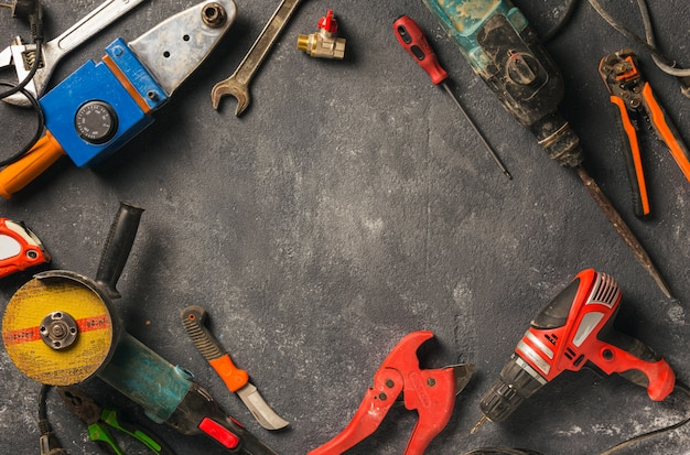 Frame of construction worker tools on a dark background top view. remodel concept