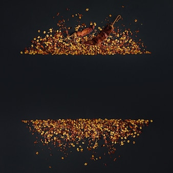 Frame of crushed red cayenne pepper, dried chili flakes and seeds on a black
