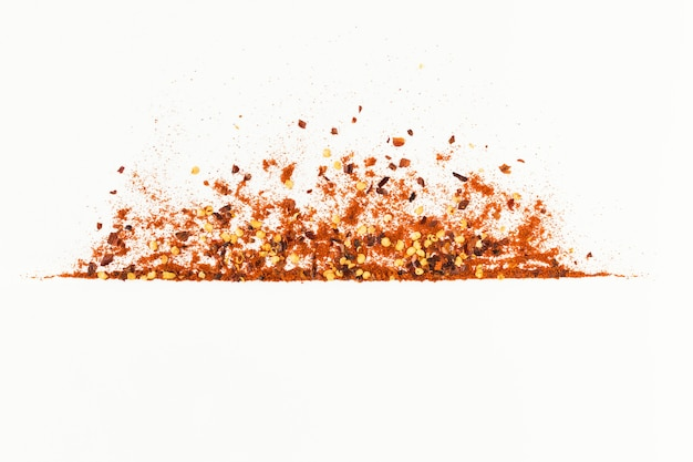 Frame of crushed red cayenne pepper, red paper paprica, dried chili flakes and seeds isolated on a white background