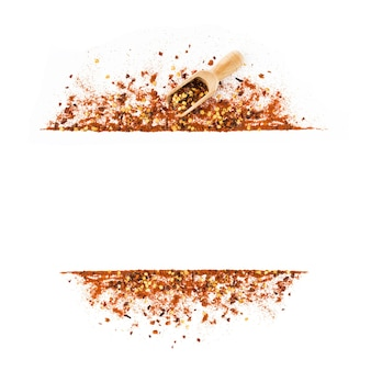 Frame of crushed red cayenne pepper, red paprica, dried chili flakes, seeds and wooden scoop isolated on a white