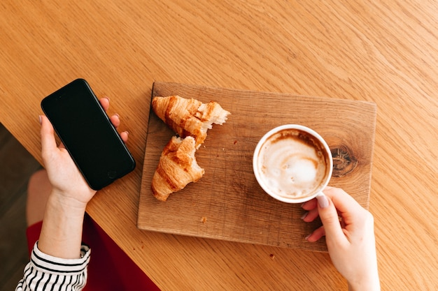 Frame above of a cup coffee with croissant on wood plate.