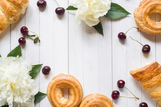 Frame custard cakes cherry peony flowers. copy space flat lay