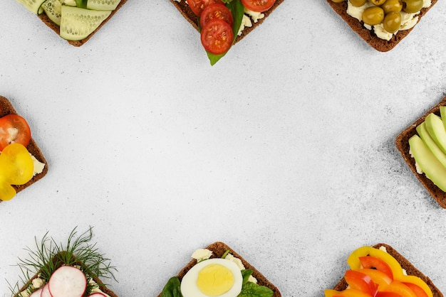 Frame of different open sandwiches on stone background with copy space. vegetables sandwiches with cheese feta. homemade open sandwiches for breakfast. top view healthy food menu.