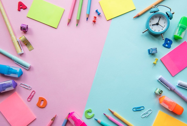 Frame of different stationery on pink and background, flat lay with space for text. back to school
