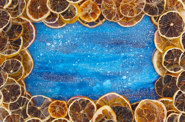 Frame of dry slices of orange and grapefruit. fruit chips on blue painted background with white splashes. festive christmas or new year design element. decorative banner.