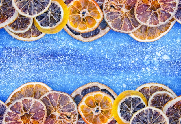 Frame of dry slices of orange and grapefruit. fruit chips on blue painted background with white splashes. festive christmas or new year design element.