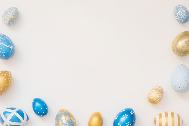 Frame of easter decorated eggs isolated on white surface.