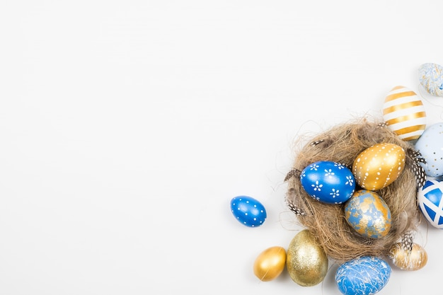 Frame of easter golden decorated eggs in nest isolated on white surface . minimal easter concept.