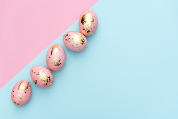 Frame of easter golden decorated eggs on pastel pink background.