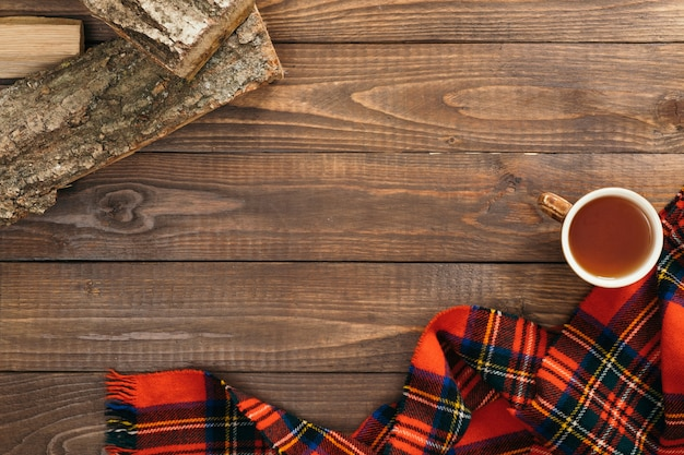 Frame of fashion feminine red scarf, cup of tea, firewood on wooden background