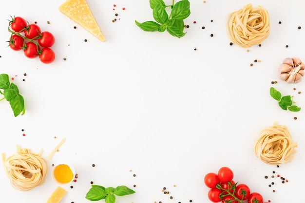Frame of fettuccine with ingredients for cooking italian pasta on white