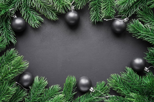 Frame of fir branches with christmas balls on a black matte background.