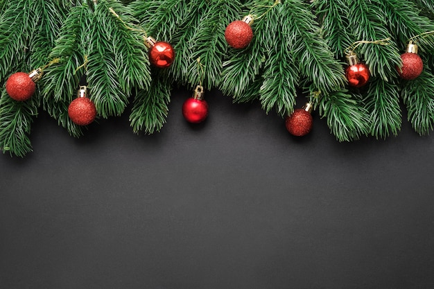 Frame of fir branches with christmas red balls on a black matte background.