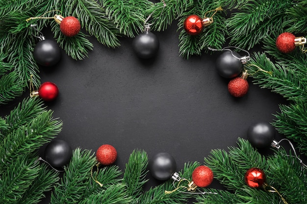 Frame of fir branches with christmas red and black balls on a black matte background.