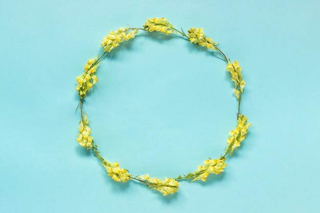 Frame floral round wreath of yellow flowers on blue background.