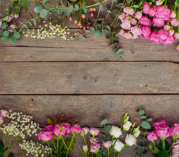 Frame of flowers on rustic wooden background with blank space for text. top view, flat lay.