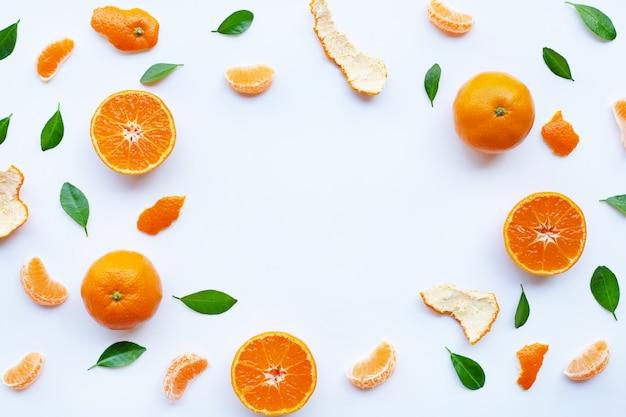 Frame of fresh orange citrus fruit with green leaves on white
