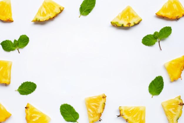Frame of fresh pineapple slices with mint leaves on white framed background
