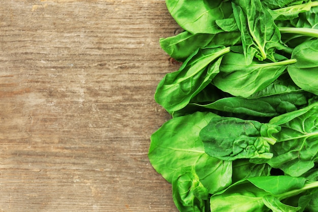 Frame of fresh spinach leaves on wooden background