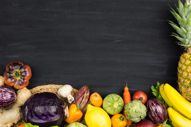 Frame of fresh vegetables and fruit on black chalk background.