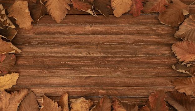 Рамка из осенних листьев на фоне стола деревянные доски