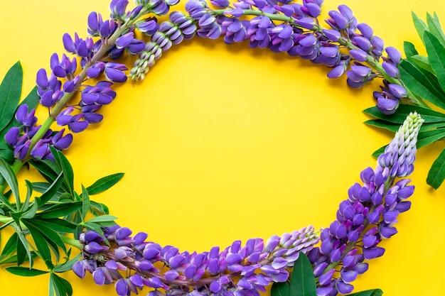 黄色の背景フラットに野生のバイオレットブルーの花の咲く紫色のルピナス組成からのフレーム
