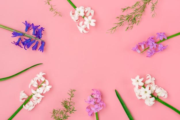 분홍색 배경에 흰색과 라일락 히아신스의 봄 꽃의 꽃다발에서 프레임 상위 뷰 평면 배치